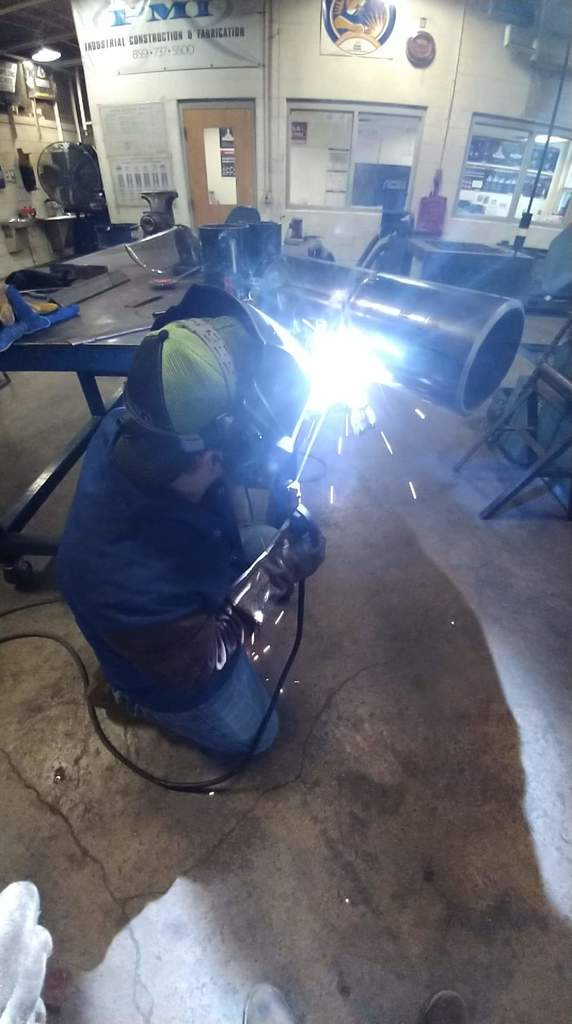 Student welding on the side of a pipe