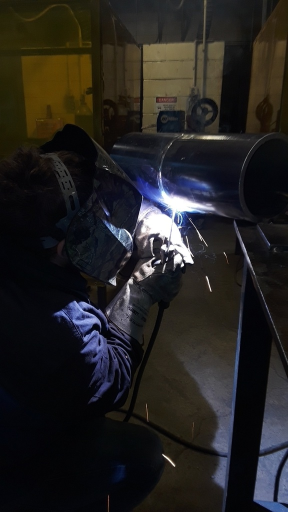 Student welding the underside of a pipe